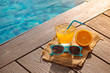 Quadro Orange fresh juice smoothie drink, sunglasses near swimming pool