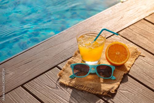 Foto Murales Orange fresh juice smoothie drink, sunglasses near swimming pool