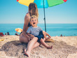 Mother with toddler under parasol on beach