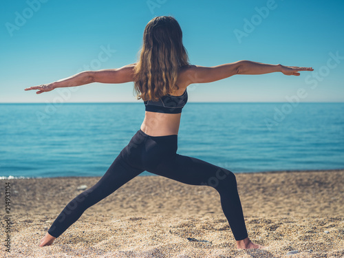 Plakat Woman in warrior yoga pose on beach