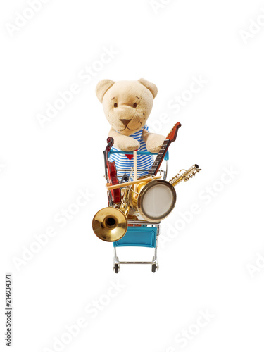 A toy bear is pushing a shopping trolley with a lot of musical instruments. Isolated on white.... - 214934371