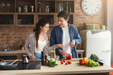 Happy couple cooking dinner together - 214936559