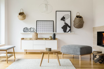 Posters and baskets on white wall in bright flat interior with wooden table next to pouf. Real photo