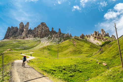 Canvas Blauw Alpine activities in Dolomites,Italy. Mountainbiking uphill on the Mountain Road in Dolomites Mountains. Rocky Mountains Ridge in the background. Cycling with bikes on track, Cortina d'Ampezzo
