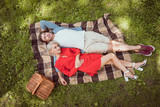 high angle view of girlfriend and boyfriend lying on blanket in park - 214953128