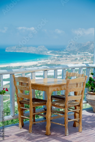 Wooden table in cafe with mountains and sea on background, Falassarna region, Crete, Greece