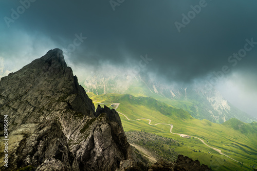 Foto Spatwand Groen blauw Italian Dolomites landscape. Light after rain in Dolomites. Rocky peaks in the background surrounded by rain clouds. Layers of forest and mountains ridge. Rocky Mountains Dolomiti. Storm rain