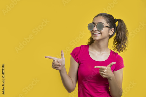 Happy, smiling girl in sunglasses on yellow background points with fingers on copy space.