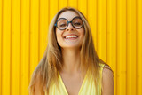 Portrait of a joyful girl wearing toy funny glasses looking up over yellow background at daylight - 214974130