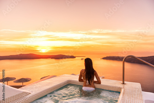 Leinwanddruck Bild Luxury travel Santorini vacation woman swimming in hotel jacuzzi pool watching sunset. Europe resort destination holiday for honeymoon getaway.