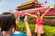 China travel tourists taking picture with photo at Forbidden City in Beijing, China. Asia trip summer vacation. Two Asian women having fun taking photos at famous chinese landmark.