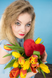 Woman holds tulips and red heart - 214994155