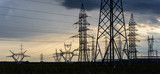 Electricity transmission pylon silhouetted against sunset sky. High voltage electric tower line - 214994193