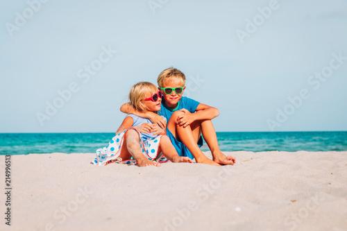 happy kids -boy and girl, brother and sister-hug on beach
