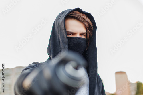 A young man with can spray in hand. Close-up. - 215004917