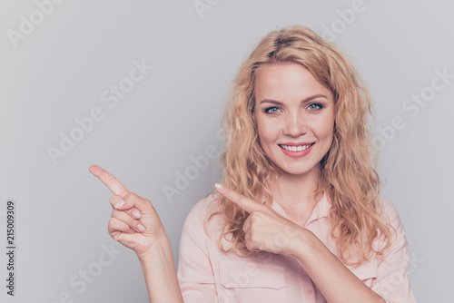 Leinwandbild Motiv Attractive cute curly-haired blonde gorgeous caucasian charming young smiling girl wearing formal wear shirt pointing fingers. Copy space. Isolated over grey background