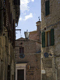 On Via Franciosa, a street of old stone buildings in Sienna Italy under a bright blue clouded sky