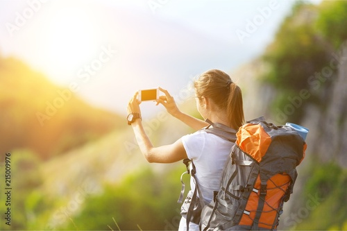 Woman with backpack trekking through mountains
