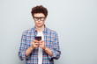 Leinwandbild Motiv Young attractive handsome guy wearing casual checkered shirt typing message in smartphone. Copy blank empty space. Isolated over grey background