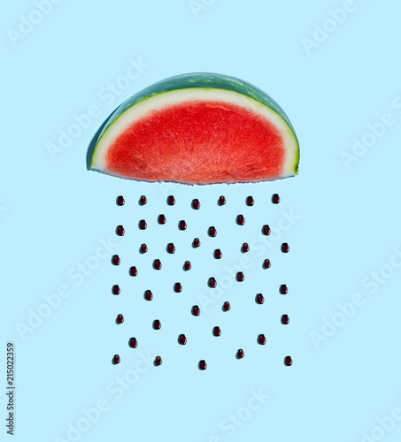 Watermelon and seeds rain concept on a blue background