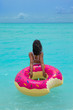 Quadro Woman with inflatable donut on the beach in summer sunny day. Summer vacation concept.
