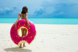 Woman with inflatable donut on the beach in summer sunny day. Summer vacation concept. - 215040100