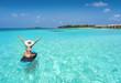 Leinwanddruck Bild - Glückliche Frau auf einen Surfbrett treibt über den türkisen Gewässern der Malediven und genießt ihren Sommerurlaub