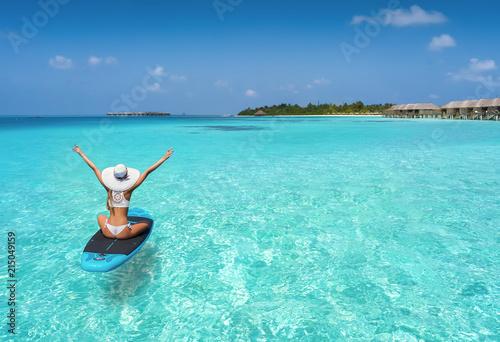 Leinwanddruck Bild Glückliche Frau auf einen Surfbrett treibt über den türkisen Gewässern der Malediven und genießt ihren Sommerurlaub