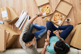 Man and woman in casual clothes sitting with crossed legs on floor at sofa and eating tasty pizza on moving day with cardboard boxes scattered around from above .