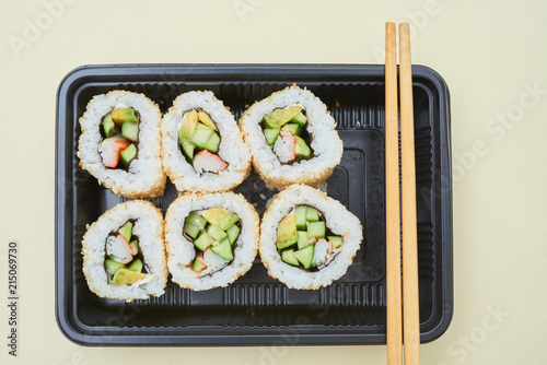 Canvas Sushi bar Top view of small black container filled with freshly made sushi and served with chopsticks on white surface