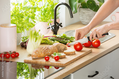 Foto Murales Woman preparing healthy breakfast, cutting a tomato in half and organic herbs and vegetables in a sunny kitchen interior