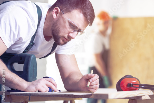 Carpenter with pencil drawing project on a wood while at work - 215081178