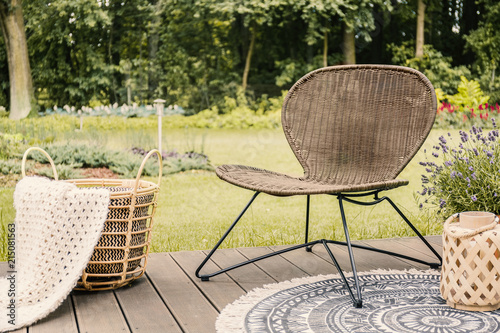 Foto Murales Close-up of a brown garden chair and a beige blanket in a basket on a wooden patio in the yard