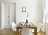 White chairs at wooden table in minimal dining room interior with door and poster. Real photo