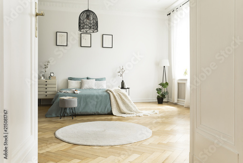 Foto Murales White round rug in spacious bedroom interior with green bed under lamp and posters. Real photo