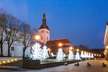 Beautiful illuminated street with cristmas trees and Saint Nicholas Church in Medieval Old Town on the morning blue hour, Tallinn, Estonia
