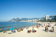 Quadro Rio residents, known as cariocas, relax at the Arpoador section of Ipanema Beach with the city skyline and Two Brothers Mountain in the background.