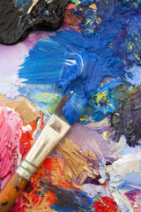 Multi coloured art oil painting palette and brush close up © ChrisAtPPS