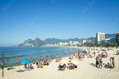 Rio residents, known as cariocas, relax at the Arpoador section of Ipanema Beach with the city skyline and Two Brothers Mountain in the background.