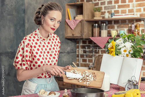 Leinwanddruck Bild beautiful adult housewife pouring sliced mushrooms into baking trey for cake and looking at camera at kitchen