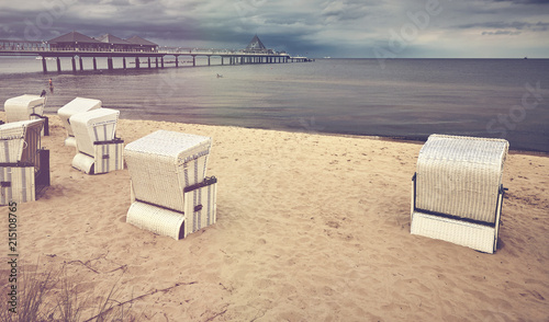 Retro stylized picture of a hooded wicker basket chairs on a beach, Heringsdorf, Germany. - 215108765