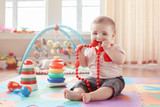 Portrait of cute adorable blond Caucasian smiling child boy with blue eyes sitting on floor in kids children room. Little baby playing with teething toys jewelry. Early education development concept. - 215112778