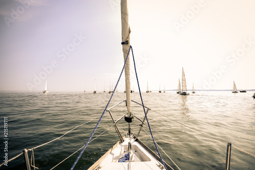 Prow of a yacht at sea with other yachts in the background in retro and vintage version.