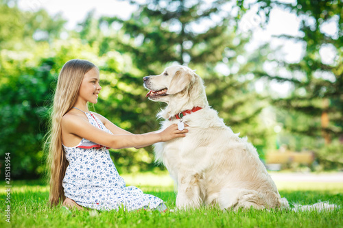 Little girl with golden retriever dog in the park
