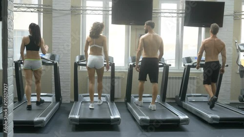 Fitness girl and guys running on treadmill at gym. Young fit people running on treadmill. Fitness and healthy lifestyle concept. © Oleksandr