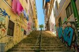 Escadaria em rua com prédios pichados