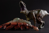 Carcharodontosaurus with a stegosaurus body nearby on dark background close up