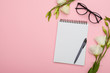 Blank note pad with eyeglasses and flowers on pink background