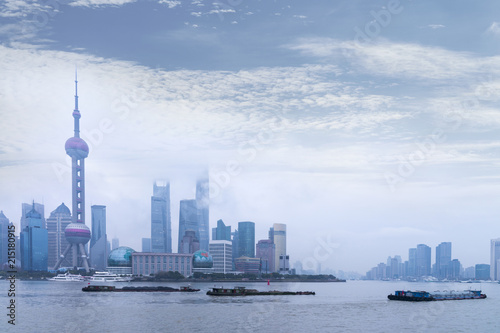 Fotobehang Shanghai Shanghai Financial Center and modern skyscraper city in misty sunrise behind pollution haze, view from the bund in Shanghai, China. vintage picture style