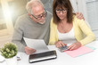Leinwandbild Motiv Senior couple checking financial document, light effect